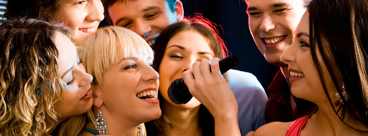 Group of friends celebrating singing into a microphone together